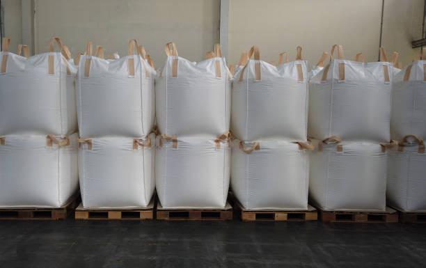 O empilhamento da carga maioria em sacos enormes é loja no armazém - foto de acervo