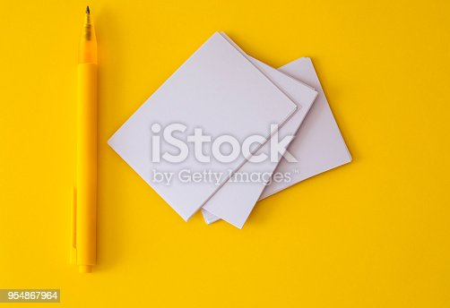 968272356istockphoto stacking of mockup empty a white business card with elegance pen  on vibrant yellow background , template for business  branding  design 954867964