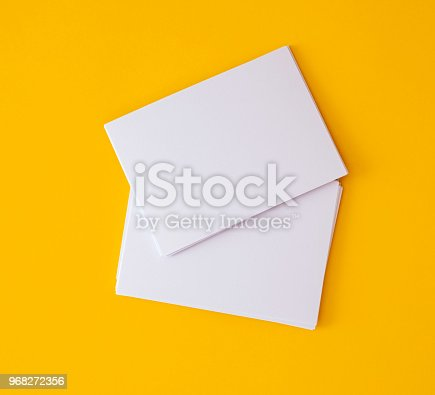istock stacking of mockup empty white business card   on vibrant yellow background , template for business  branding  design 968272356