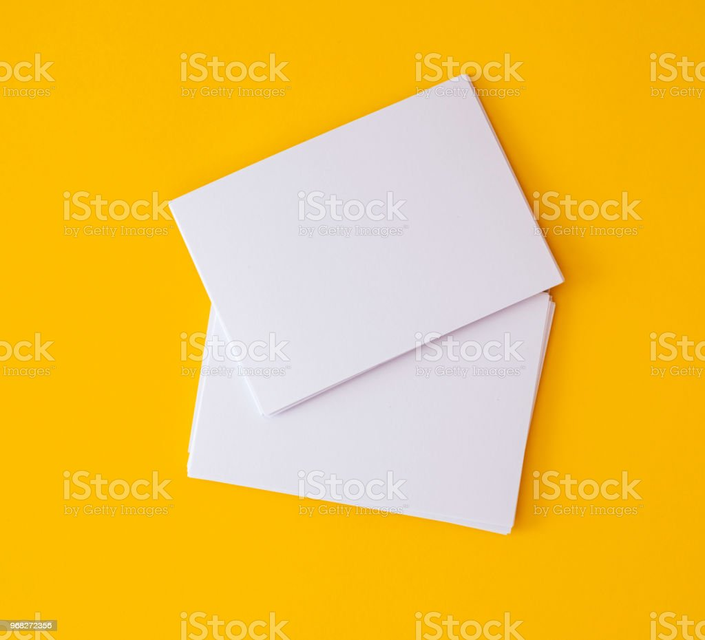 stacking of mockup empty white business card   on vibrant yellow background , template for business  branding  design stock photo