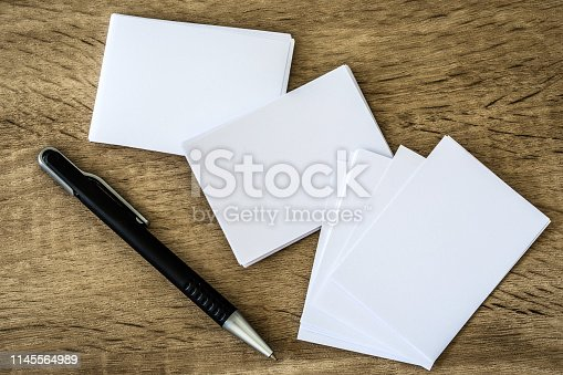 968272356istockphoto stacking of mockup empty white business card with a elegance pen  on wooden background , template for business  branding identity design 1145564989