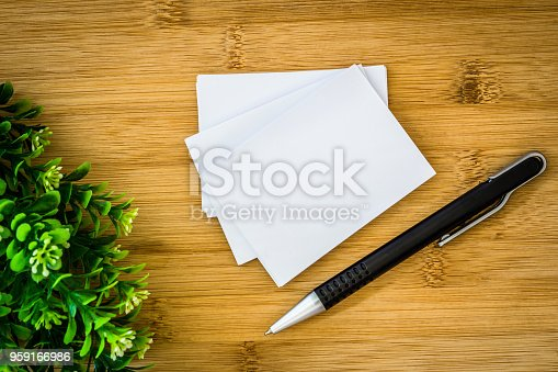 968272356istockphoto stacking of mockup empty white business card with elegance pen  on wooden background , a template for business  branding identity design 959166986