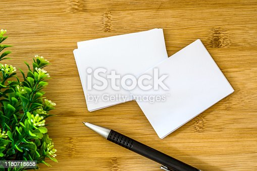 968272356istockphoto stacking of mockup empty white business card with elegance pen  on wooden background , template for a business  branding identity design 1180718658