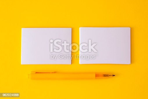 968272356istockphoto stacking of mockup empty white business card with elegance pen  on vibrant yellow background , a template for business  branding  design 962024588
