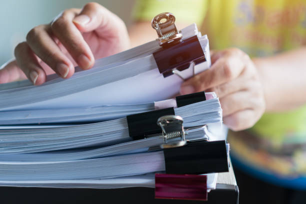 Stacks documents of paper files, Businessman hands working in messy bureaucracy and searching information on office, Accounting budget report file, arranging unfinished of paperwork on busy overwork stock photo