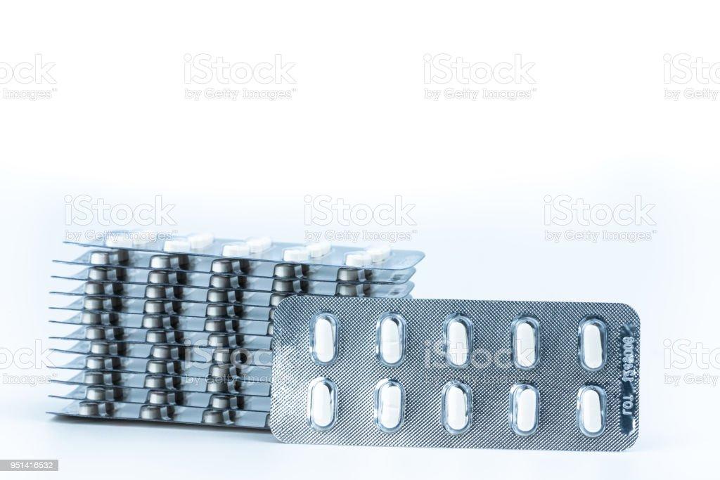 Stacks of anti allergy pills in blister packs isolated on white background. Pharmaceutical market. Cetirizine : antihistamine tablets. Pharmaceutical industry. Healthcare budgets. Drug pricing. stock photo