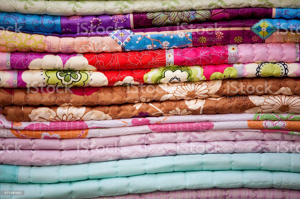 Stacks of Bedding Quilt Fabric at Outdoor Flea Market Stand royalty-free stock photo