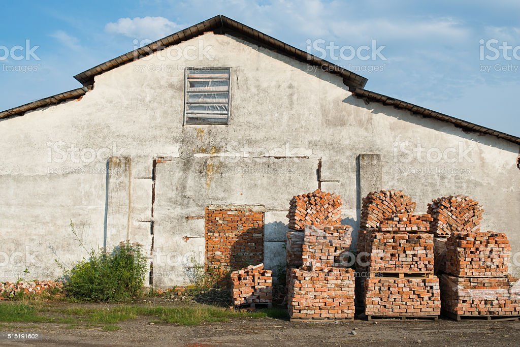 Stacks of bricks near the old house stock photo