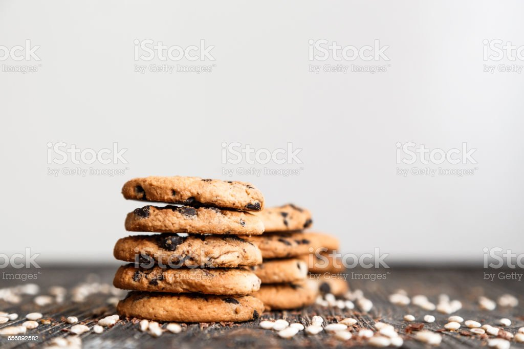 Stacks of chocolate chip cookies on dark table with copy space on top stock photo