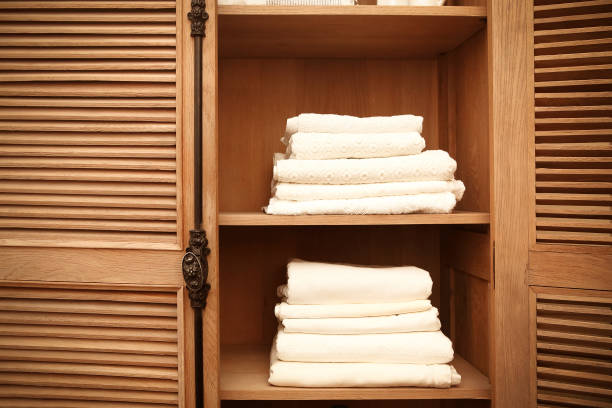 Stacks of clean white soft towels in cupboard in room stock photo