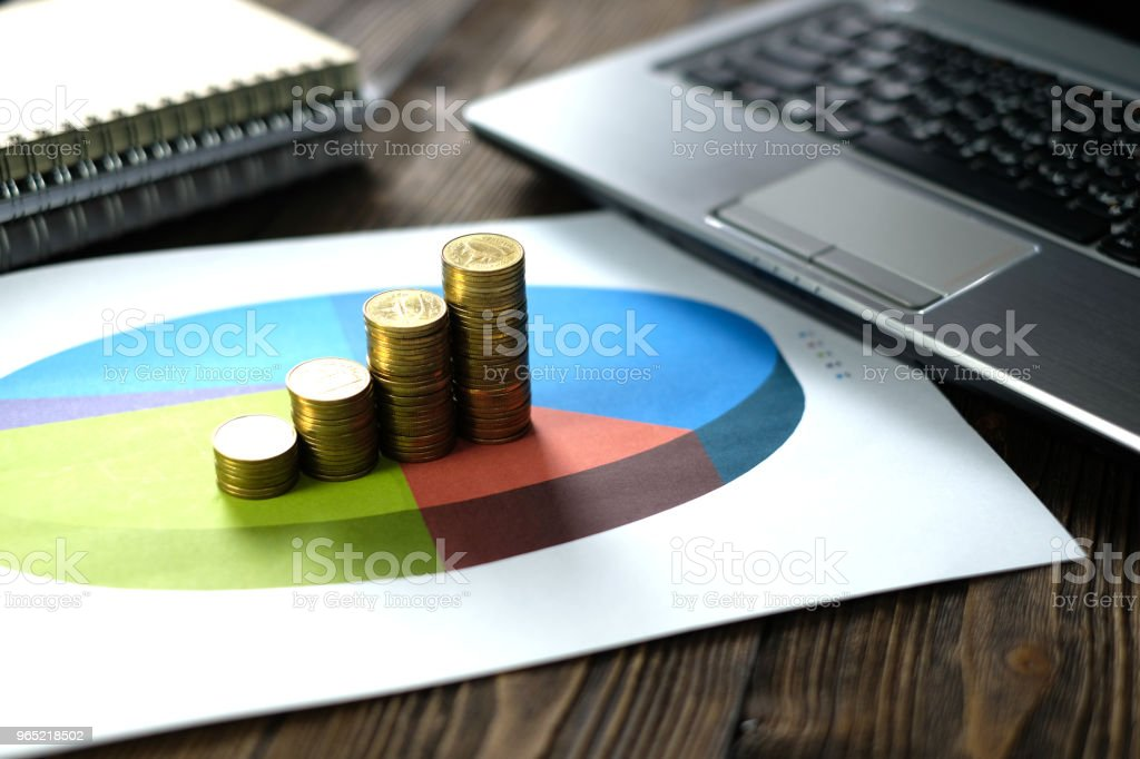 Stacks of coin with notebook laptop computer and financial graph on white paper on working table, business planning vision and finance analysis concept. royalty-free stock photo