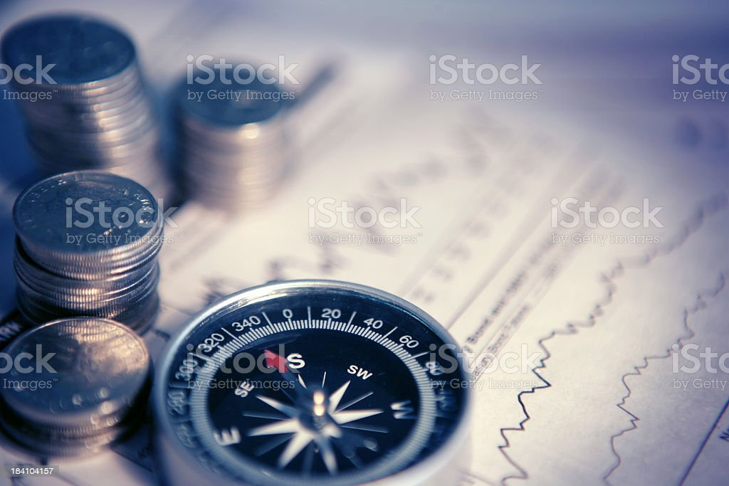 Stacks of coins, a compass and documents signaling finances stock photo