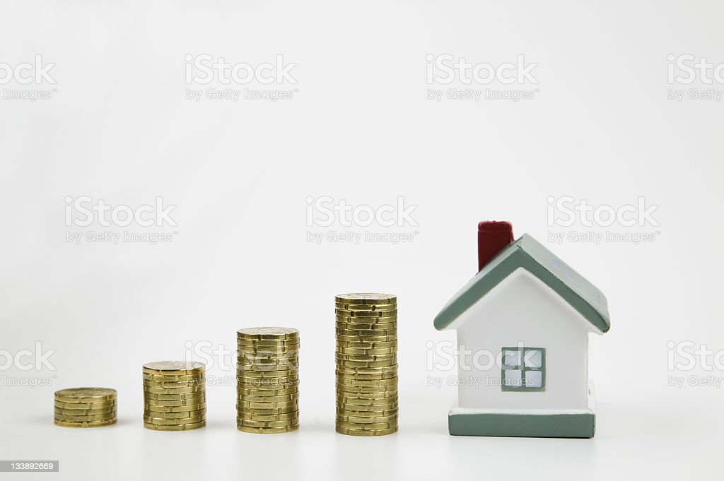 Stacks of coins and a miniature house  stock photo