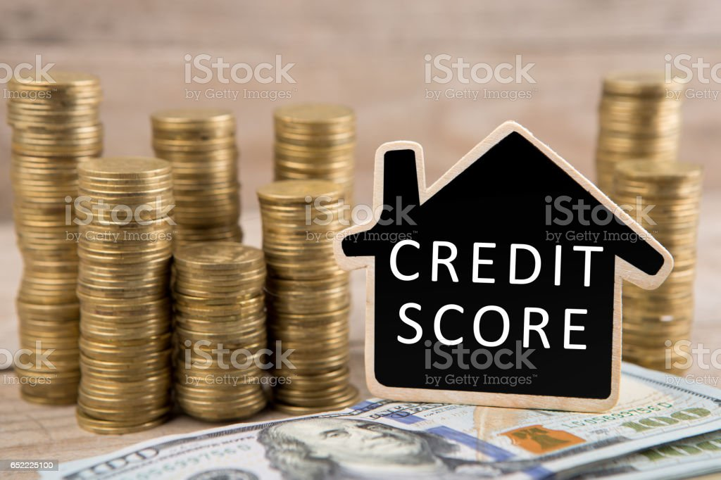 Stacks of coins and dollars, blackboard with text 'CREDIT SCORE' stock photo