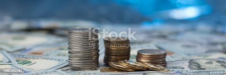 Stacks of coins on scattered hundred dollar bills on a blue background