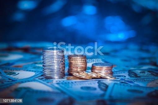 istock Stacks of coins on the background of one hundred dollar bills. Dark blue light. 1071354126
