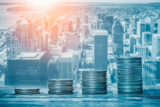 Stacks of coins with cityscape or skyline in the background. Financial growth, real estate sector prices, municipal budget or city funds, economy or banking concepts. stock photo