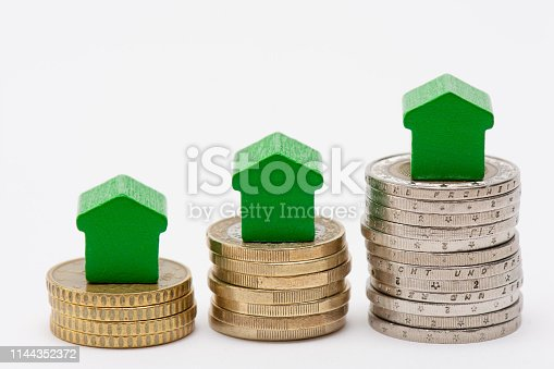 istock Stacks of coins with green arrow shaped houses on top 1144352372