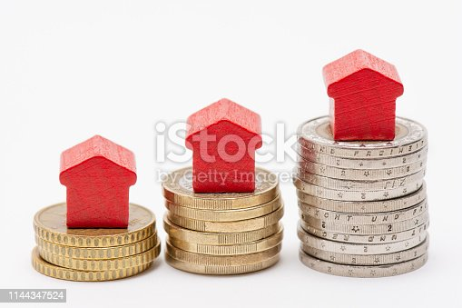 istock Stacks of coins with red arrow shaped houses on top 1144347524