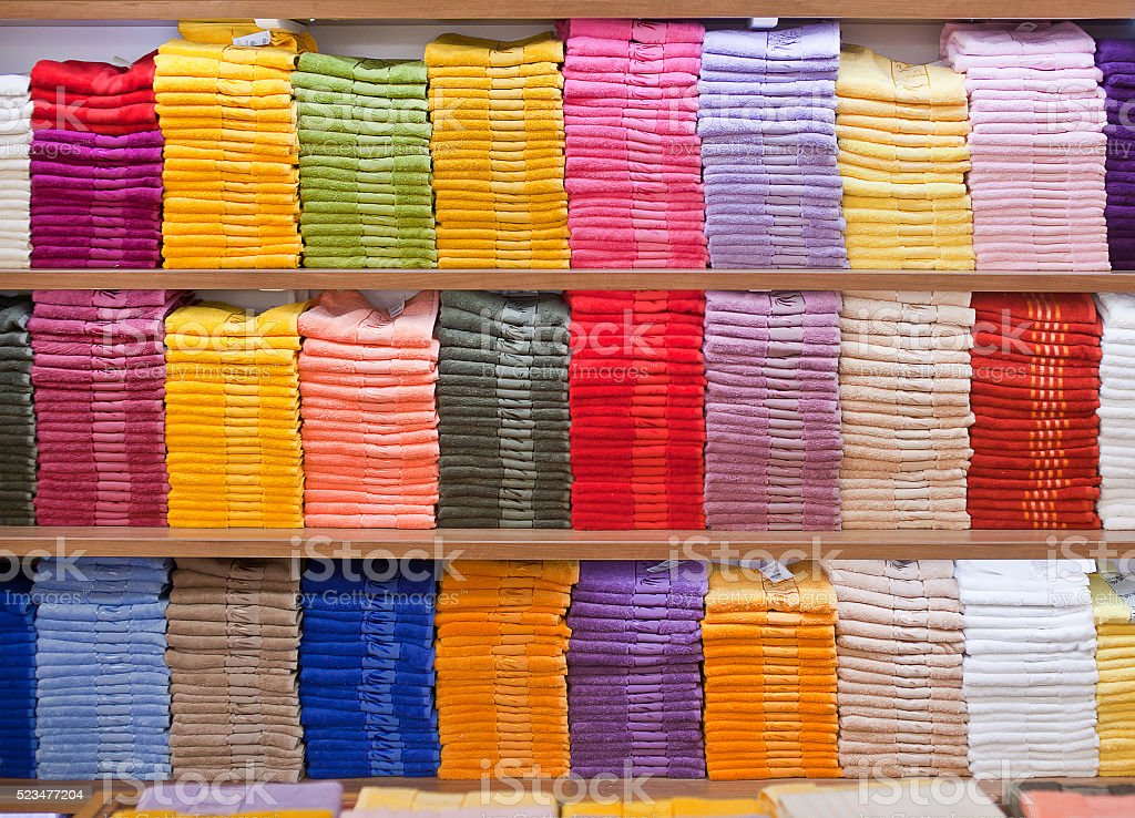 Stacks of colored terry towels on the shelves stock photo