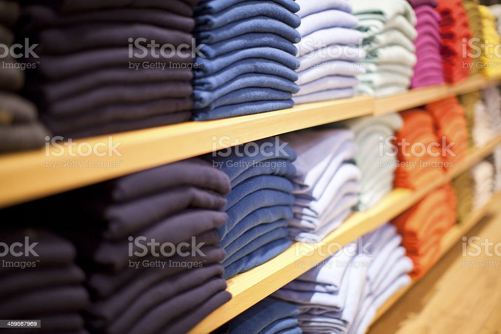 Stacks of different colored sweaters on store shelves stock photo