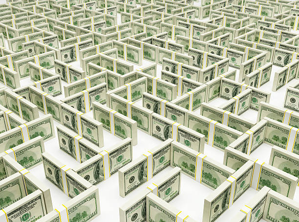 Stacks of dollar bills propped up to form a financial maze stock photo