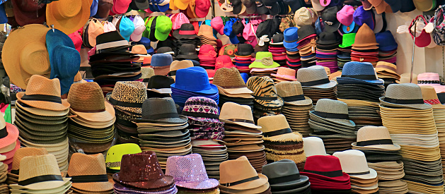 Stacks of fashionable hats in different styles and colors in the hat shop