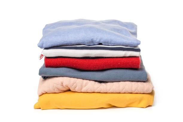 pilas de ropa doblada sobre fondo blanco - vestimenta fotografías e imágenes de stock