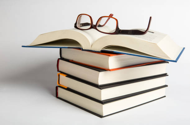 Stacks of hardback books with reading glasses. Reading concept. copy space. A collection of books read stock photo