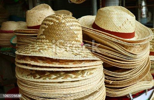 Stacks of natural color beautiful straw hats in the hat shop