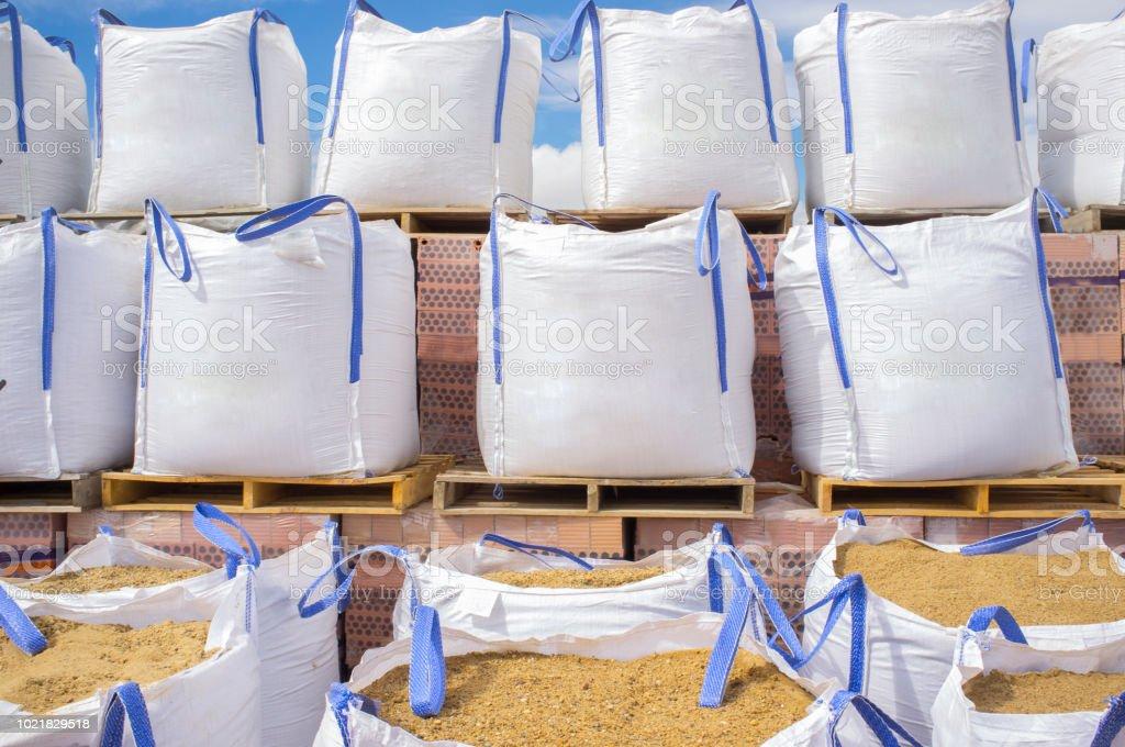 Stapel von Bast großen Sandsäcken gestapelt über Holzpaletten mit Steinen – Foto