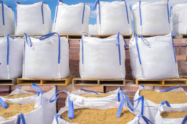 Stacks of raffia large sand sacks stacked over wooden pallets with bricks stock photo