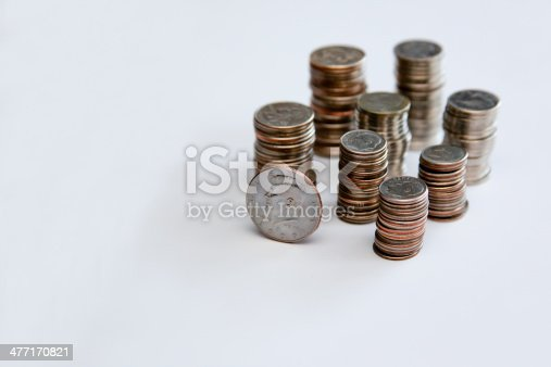 Quarters, nickels, dimes all stacked up with a Kennedy Half dollar sitting up on its edge in the front of the stacks, all on a white background