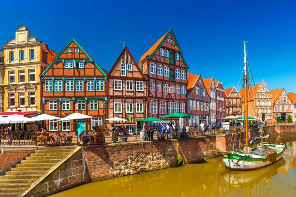 Stade, Germany: Cityscape of a small, beautiful German town with the traditional half-timbered architecture and canal with an old wooden sailboat stock photo