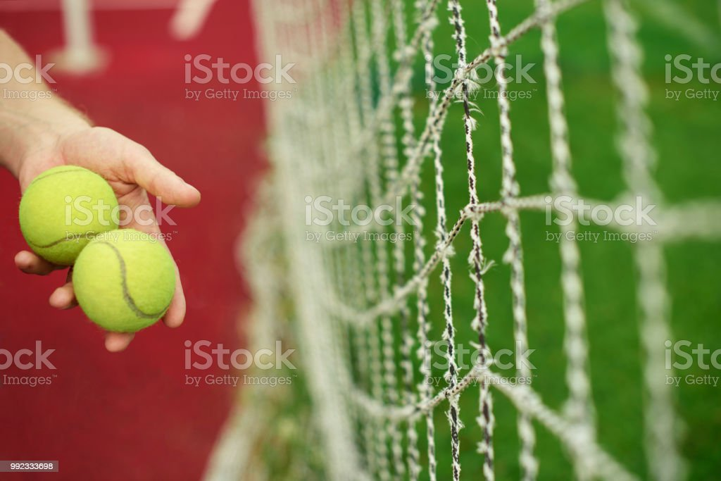 Close up of tennis balls in hands on tennis court.