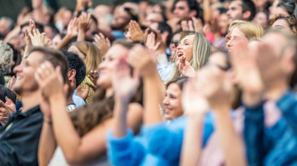 Stadium crowd cheering and clapping Large group of people on a stadium cheering and clapping during a sports match. spectator stock pictures, royalty-free photos & images