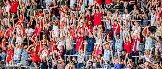 Large group of people raising their hands on a stadium during a sports match. Some are wearing red jerseys.