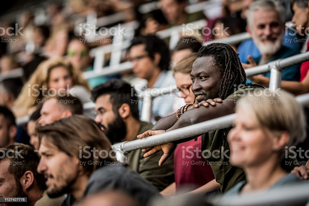 Stadium crowd watching a sports match with the focus on a young...