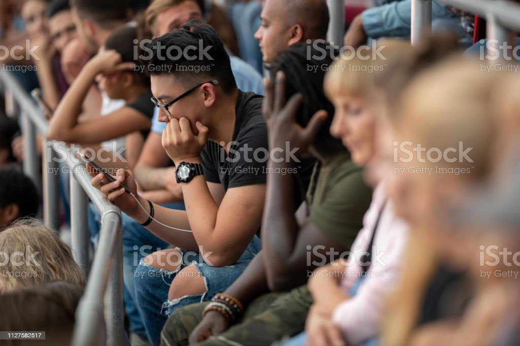Side view of a group of people sitting on stadium bleachers during a...