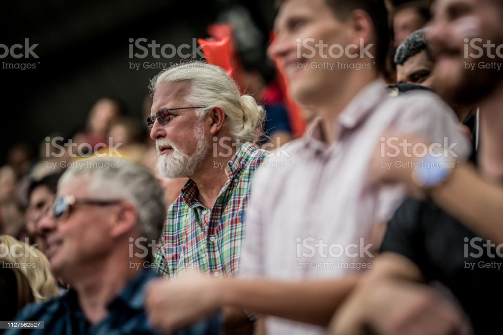 Large group of people in stadium bleachers during a sports match with...