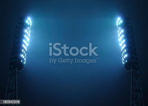 Stadium floodlights against a dark night sky background with copy space