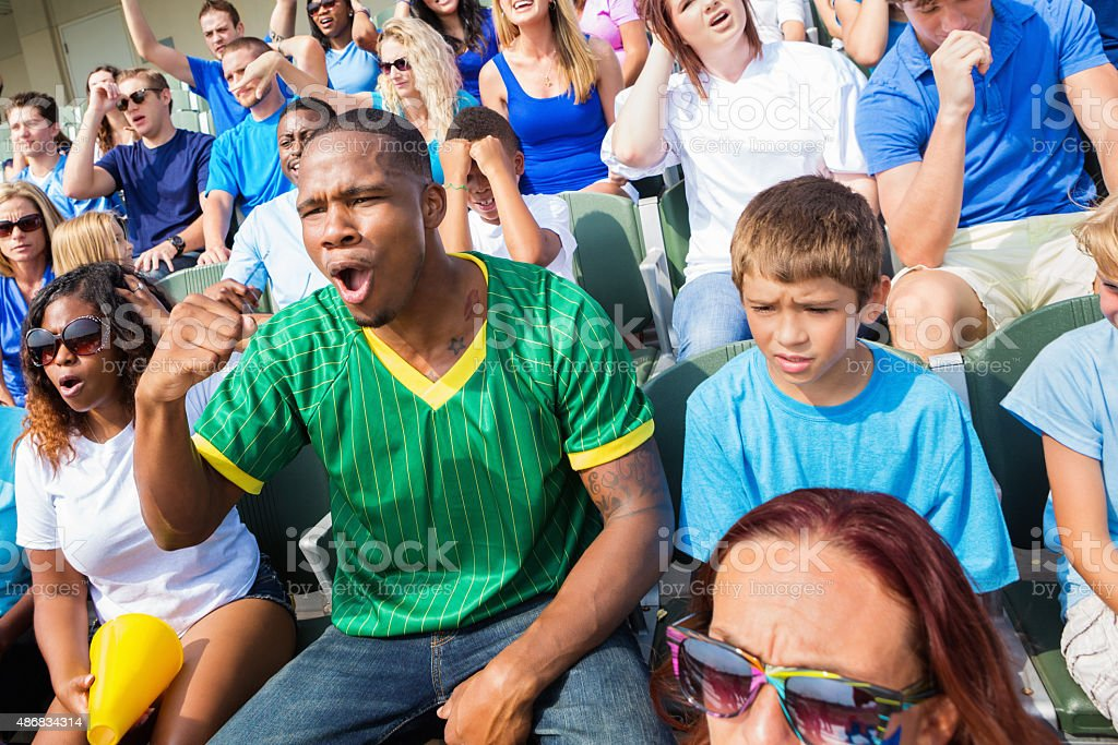 Young adult African American man is cheering for his favorite sports...