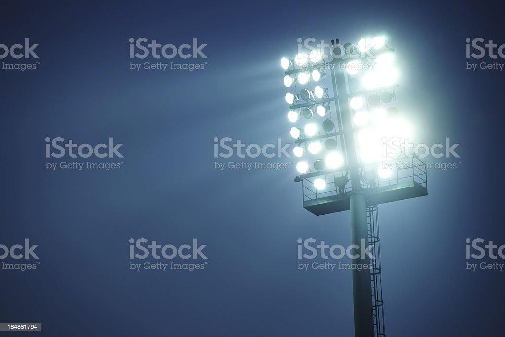 Stadium lights against dark blue sky  - front view stock photo