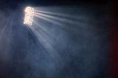 istock stadium lights and smoke against dark night sky background 1199913201