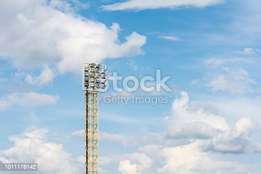 508552962istockphoto Stadium lights pole with blue sky and clouds. 1011176142