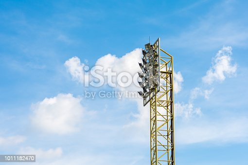 931661614istockphoto Stadium lights pole with blue sky and clouds. 1011182470