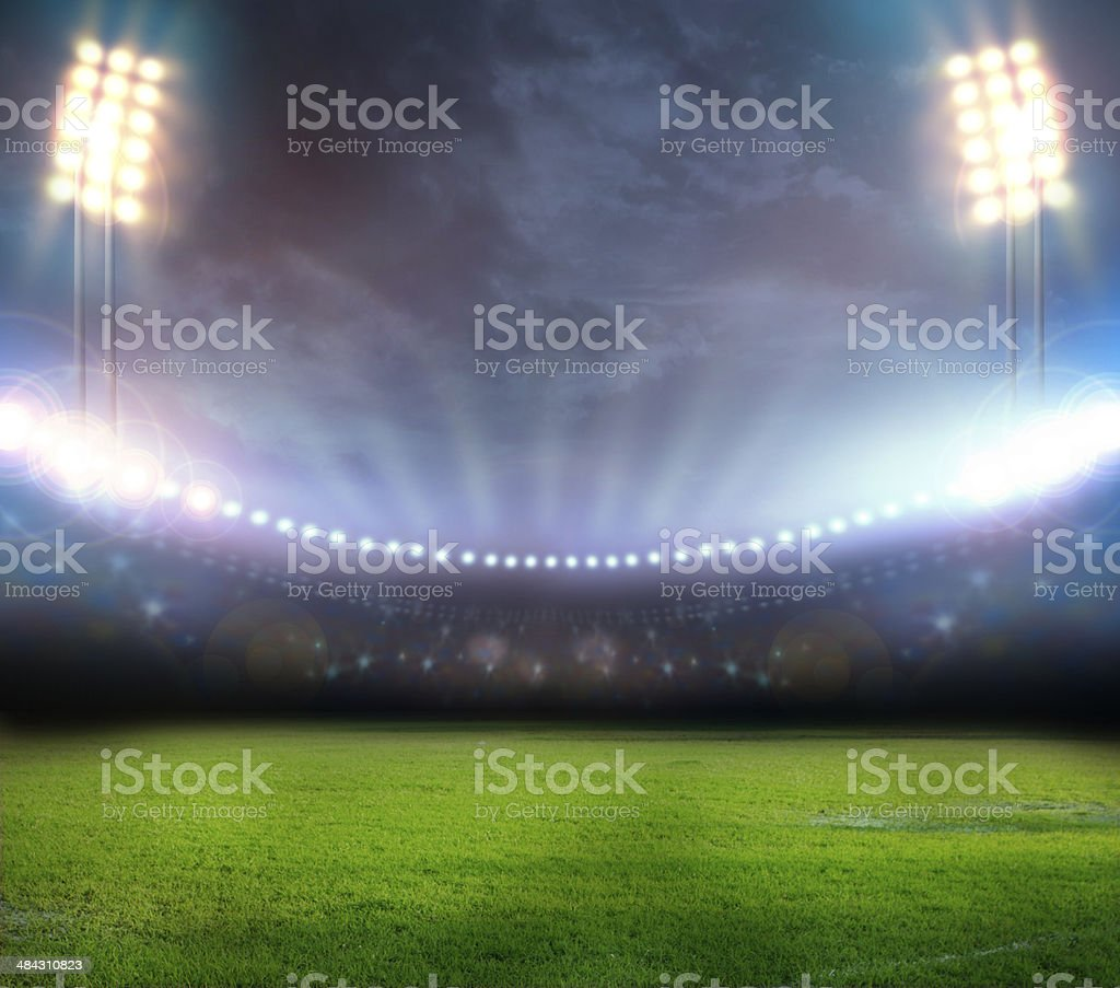 Stadium lights shining down on field stock photo