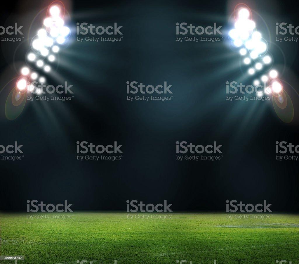 Stadium lights shining on field at night stock photo