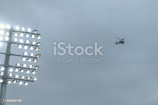Stadium lights turned on and helicopter