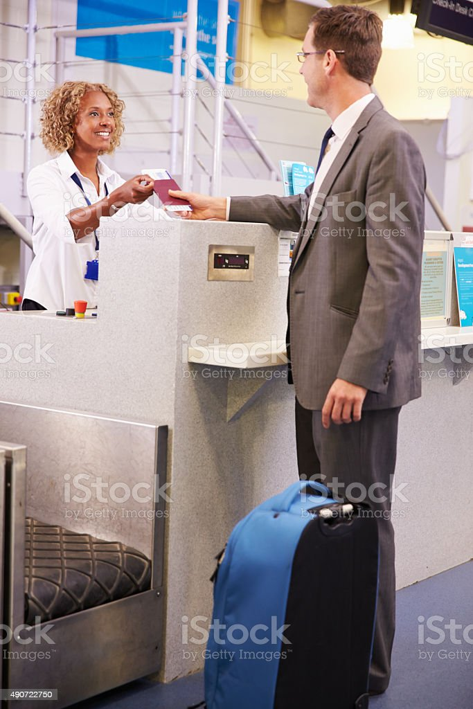 Staff At Airport Check In Desk Handing Ticket To Businessman stock photo
